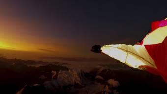 Nur ihr Wingsuit und die ersten Bergspitzen sind beleuchtet: Géraldine Fasnachts traumhafter Sprung über den Walliser Alpen.