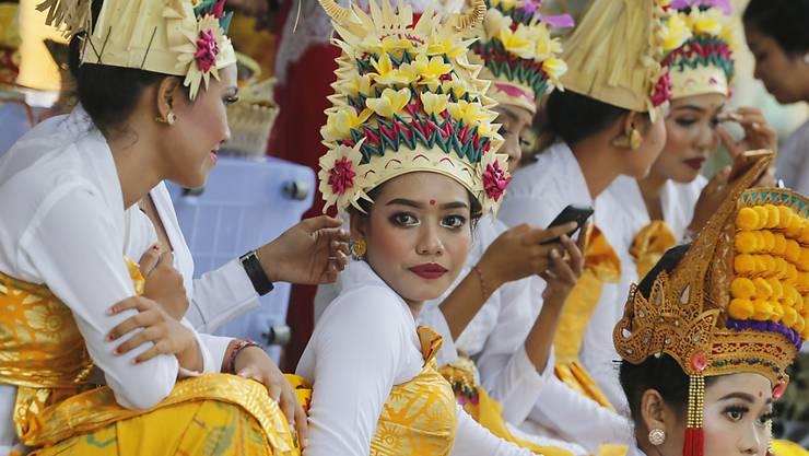 ARCHIV - Tänzerinnen und Tänzer in traditioneller Kleidung in einem Hindu-Tempel auf Bali. Foto: Firdia Lisnawati/AP/dpa
