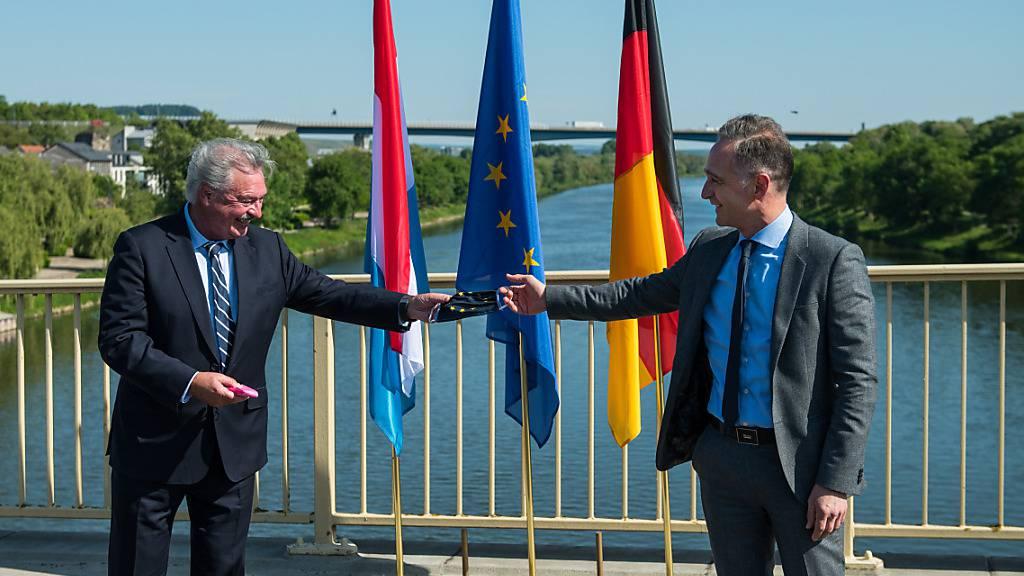 ARCHIV - Bundesaußenminister Heiko Maas (r) überreicht im Mai seinem Luxemburger Amtskollegen Jean Asselborn auf der Brücke über die Mosel, die das saarländische Perl und das Luxemburger Schengen verbindet, einen Mundschutz. Foto: Oliver Dietze/dpa/Archiv
