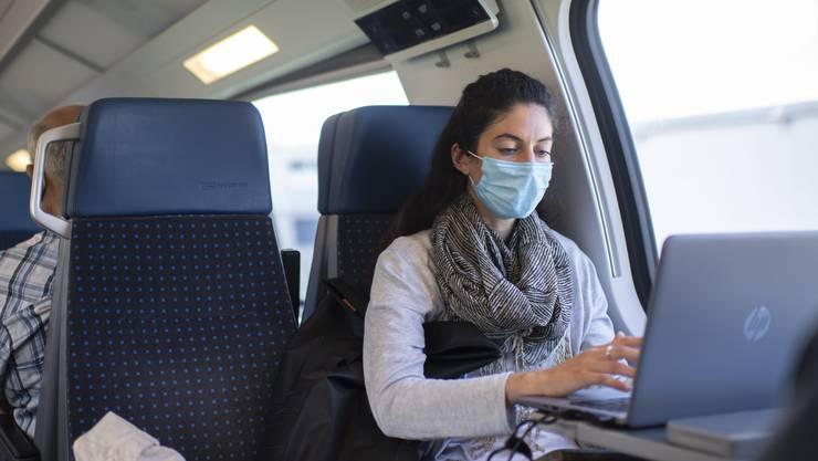 Eine Frau mit Schutzmaske im Zug