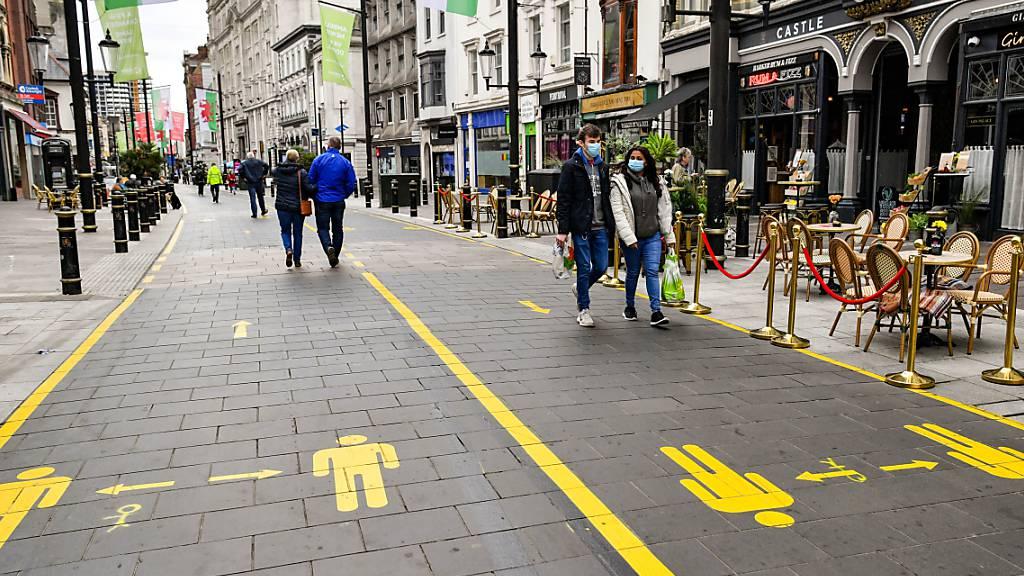 dpatopbilder - Nachdem die walisische Regierung für drei weitere Gebiete von Wales aufgrund steigender Corona-Zahlen lokale Lockdowns angeordnet hat, tragen die Menschen in Cardiff Gesichtsmasken. Foto: Ben Birchall/PA Wire/dpa