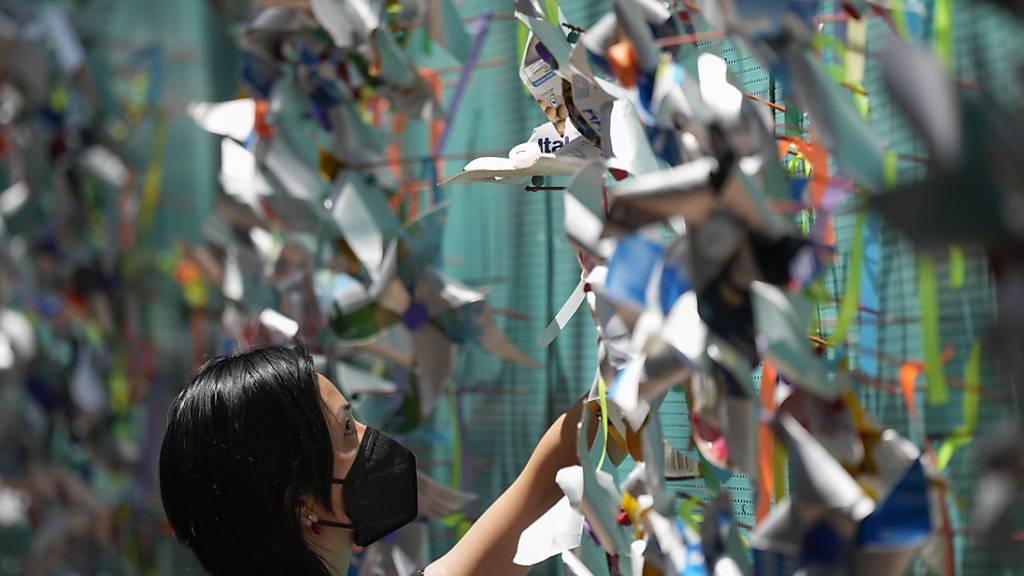 Eine Frau hängt während einer Gedenkveranstaltung Stecknadelräder im Gedenken an Corona-Opfer an eine Wand in Sao Paulo. (Archivbild) Foto: Andre Penner/AP/dpa
