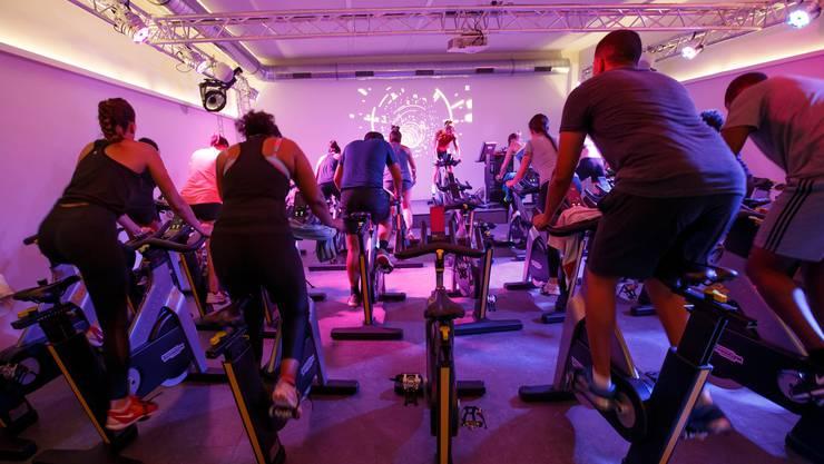 Spinning-Gruppe trainiert in einem Fitness Center in Genf. Die Romands fühlen sich körperlich weniger fit als die Deutschschweizer.