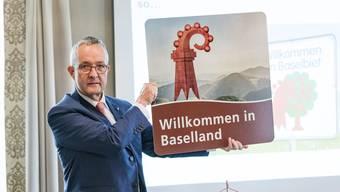 Wie sieht die künftige Tourismus-Signalisation im Baselbiet aus? Im Baselbieter Rütli (=Bad Bubendorf) wird das Geheimnis gelüftet. Präsentiert wurde die neue Signalisation von RR Thomas Weber (im Bild), hier mit dem neuen Schild, Tobias Eggimann (Baselland Tourismus) und Nic Kaufmann (2. Landschreiber)