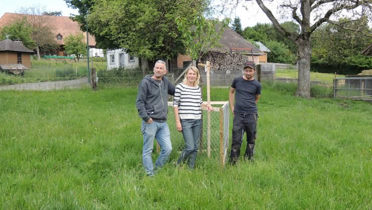 Simone und Reto Hirter mit dem Gartenbauer, Benjamin Ramser, bei neugepflanztem Baum