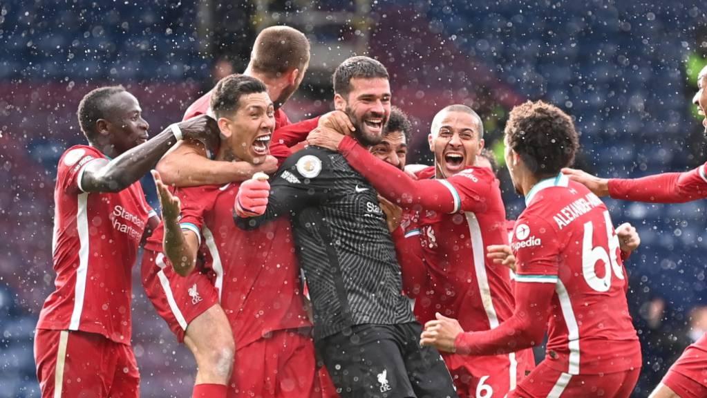 Die Liverpooler feiern Goalie Alisson und dessen späten Siegtreffer.