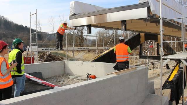 Auen-Renaturierung Rietheim: Die erste der beiden Holzbrücken über den Chly Rhy wird eingesetzt.