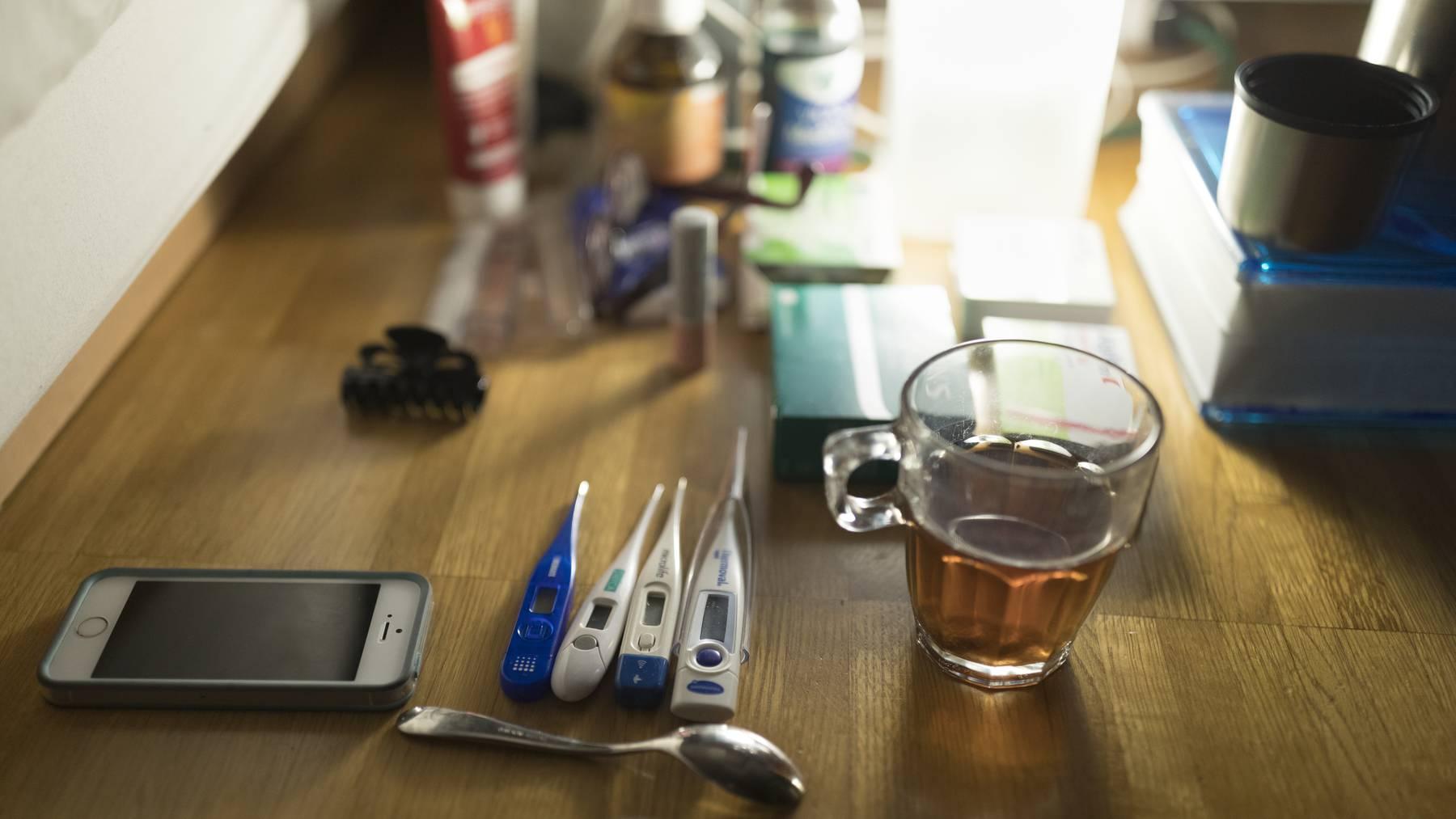 Verschiedene Medikamente gegen Grippe und Husten, sowie Tee und Thermometer stehen neben einem Bett in Zuerich, aufgenommen am 28. November 2016.