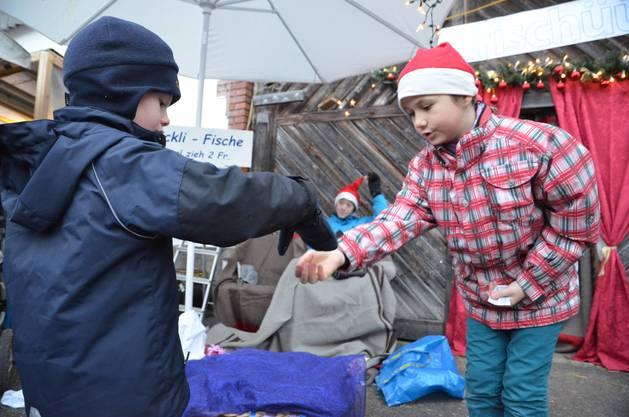Das Päckli-Fischen lockte zahlreiche Kinder an - Fabienne nimmt gerade den Batzen des Buben entgegen, der nachher ein Päckli fischen darf