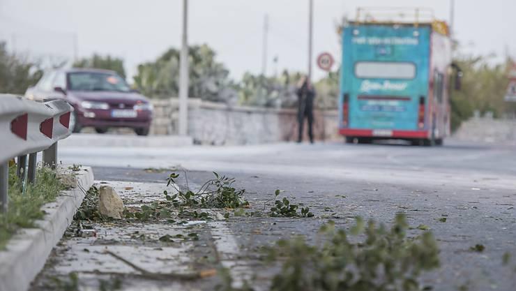 Äste am Boden nach dem Unfall mit dem Doppeldeckerbus (hinten) auf Malta.