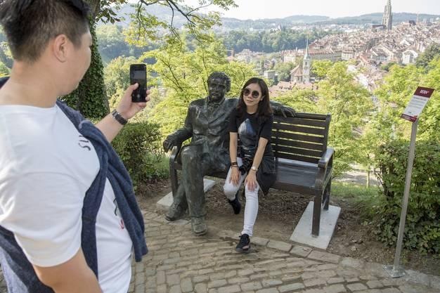 Eine Chinesische Touristin posiert mit einer Albert Einstein Bronzestatue auf einer eben solchen Bank vor dem Hintergrund der Berner Altstadt am Samstag, 26. August 2017 in Bern. (KEYSTONE/Lukas Lehmann)