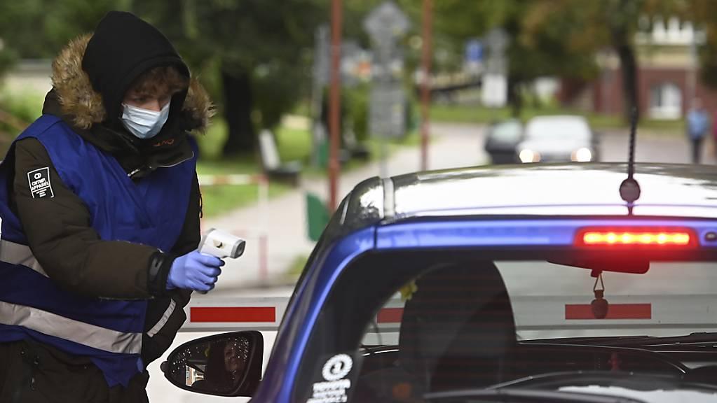 ARCHIV - Eine Mitarbeiterin misst am Eingang zum Universit‰tsklinikum TrencÌn, Slowakei, die Kˆrpertemperatur einer Frau im Auto. Foto: Radovan Stoklasa/TASR/dpa