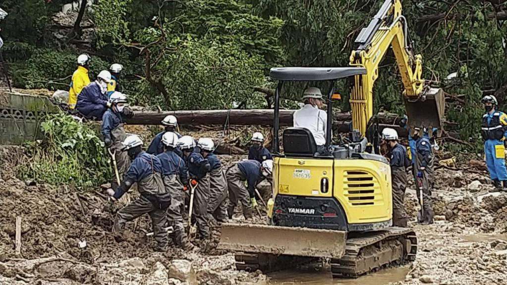Feuerwehrleute suchen nach schweren Regenfällen in einem Gebiet im Obama-Viertel von Unzen, Präfektur Nagasaki, Südjapan, nach vermissten Personen.