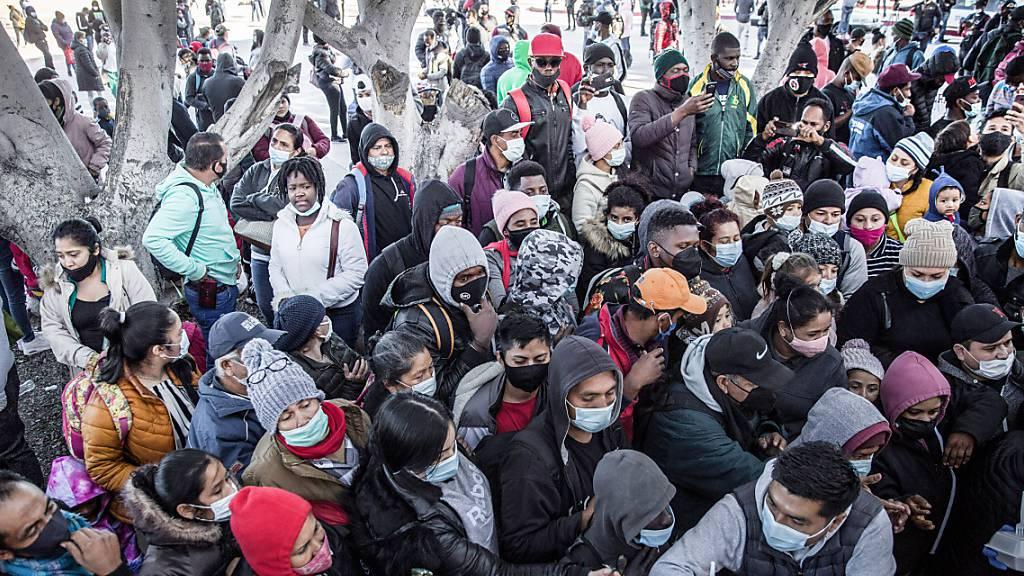 Migranten warten darauf, dass Nahrung und Wasser am Grenzübergang zwischen Mexiko und den USA in Tijuana verteilt werden (Archiv).