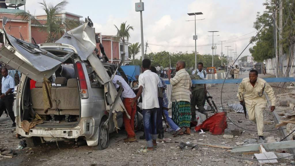 Ein somalischer Polizist kämpft sich durch die Wrackteile beim Sahafi Hotel in Mogadischu. (KEYSTONE/AP Photo/Farah Abdi Warsameh)