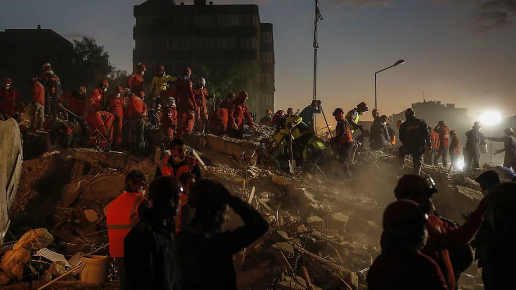 Mitglieder des Rettungsdienstes suchen in den Trümmern eines eingestürzten Gebäudes in Izmir nach Überlebenden. Foto: Darko Bandic/AP/dpa