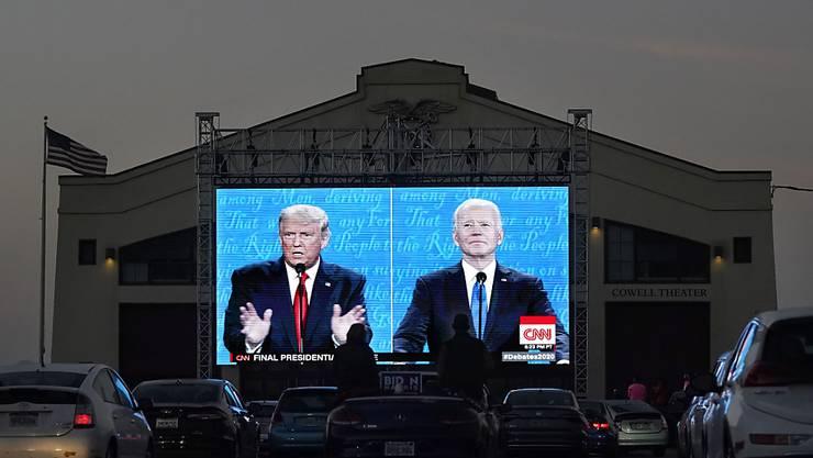 Menschen verfolgen das letzte TV-Duell vor der Präsidentschaftswahl auf einer Leinwand im Fort Mason Center. Foto: Jeff Chiu/AP/dpa