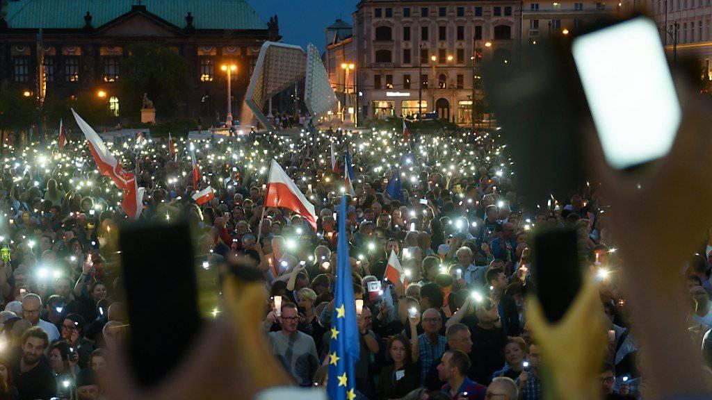 Mit Kerzen und Handylicht: In mehreren Städten gehen Polen am Sonntag auf die Strasse, um gegen die Justizreform zu protestieren.