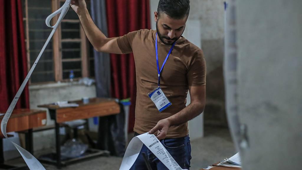 Ein Mitarbeiter des Wahlausschusses zählt Stimmen für die irakischen Parlamentswahlen in einem Wahllokal aus. Unter einem Großaufgebot an Sicherheitskräften hat im Irak am Sonntag (10.10.21) die Parlamentswahl stattgefunden. Foto: Ameer Al Mohammedaw/dpa