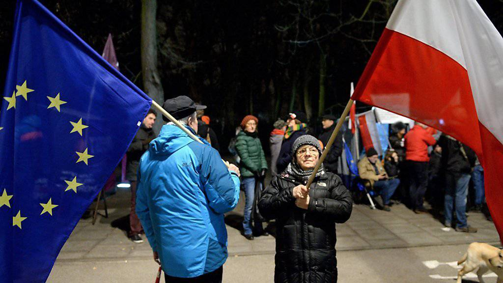 Demonstrierende in Warschau mit den Flaggen Polens und der EU (Archiv)