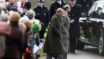 Prinz Philip (im grünen Mantel) und Prinz Edward schreiten zur Kirche in Sandringham