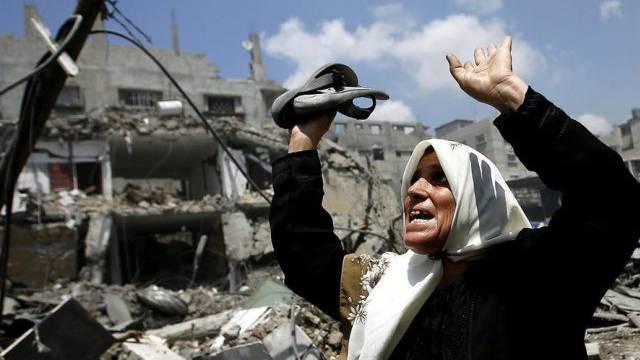 Frau vor einem zerstörten Haus in Gaza (Symbolbild)