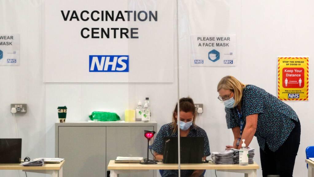 ARCHIV - Mitarbeiterinnen arbeiten in einem Impfzentrum in der Kathedrale von Blackburn. In Großbritannien sind mittlerweile drei Viertel der Erwachsenen vollständig gegen Corona geimpft. Premierminister Boris Johnson bezeichnete das am Dienstag auf Twitter als «riesigen nationalen Erfolg». Foto: Peter Byrne/PA Wire/dpa