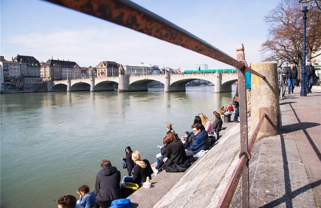 Lebensqualität sieht anders aus: Basler sitzen wie Sardinen am schmutzigen Rhein und träumen von der Ferne.