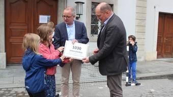 Stadtpräsident Hanspeter Hilfiker und Stadtschreiber Daniel Roth (r.) nehmen die Petition entgegen.
