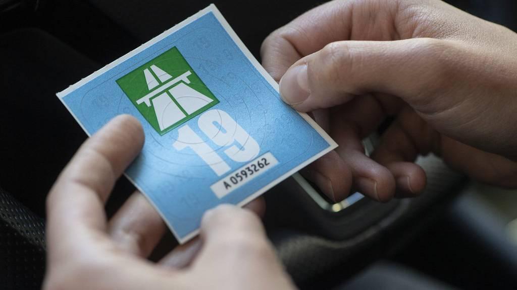 Eine Frau klebt die  Autobahnvignette fuer das Jahr 2019 an die Windschutzscheibe ihres Fahrzeuges, aufgenommen am Mittwoch 12. Dezember 2018 in Zuerich. (KEYSTONE/Ennio Leanza)