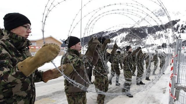 Angehörige der Schweizer Armee montieren im Vorfeld des WEF 2011 Abschrankungen in Davos