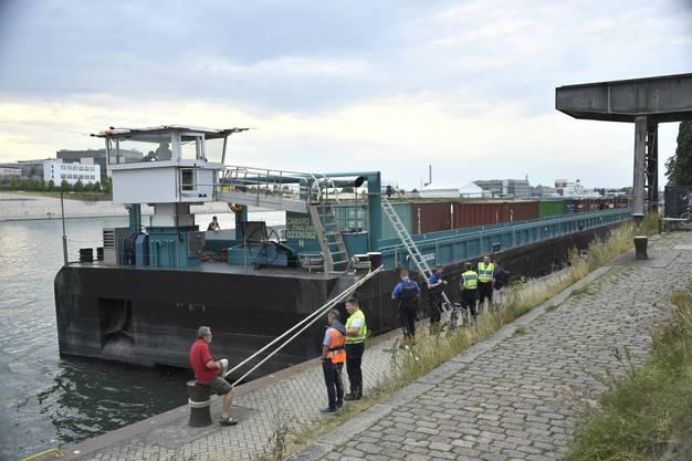 Einsatzkraefte von Polizei und Feuerwehr stehen am Rhein bei einem Frachtschiff, am Donnerstag, 18. Juli 2019 in Basel. Auf dem Rhein ist das Schiff mit der Mittleren Brücke kollidiert und danach in die Johanniterbrücke gekracht – es hat scheinbar die Kontrolle verloren. Die Unfallursache ist gemaess Polizeiangaben noch unklar. (KEYSTONE/Georgios Kefalas)