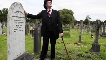 """ARCHIV - James Joyce-Darsteller John Shevlin steht am Grab des Schriftstellers John Stanislaus Joyce und seiner Frau Mary Jane beim traditionellen """"Bloomsday"""" auf dem Glasnevin-Friedhof. Foto: Brian Lawless/PA Archive/dpa"""