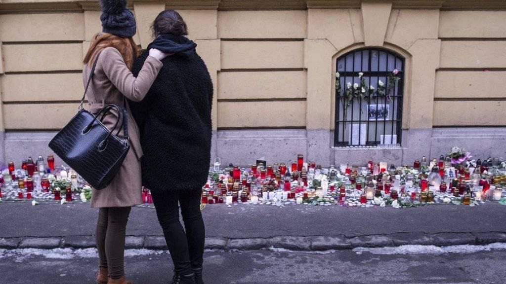 Eine Überlebende des Busunglücks und ein anderes Mädchen stehen vor Blumen und Kerzen beim Budapester Gymnasium, wo die meisten der Opfer zur Schule gingen.
