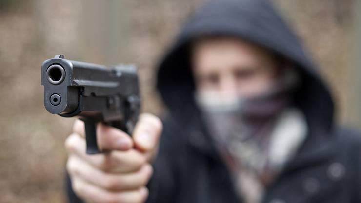 Der maskierte Mann bedrohte die allein anwesende Verkäuferin mit einer Faustfeuerwaffe und verlangte die Herausgabe von Bargeld. (Symbolbild)