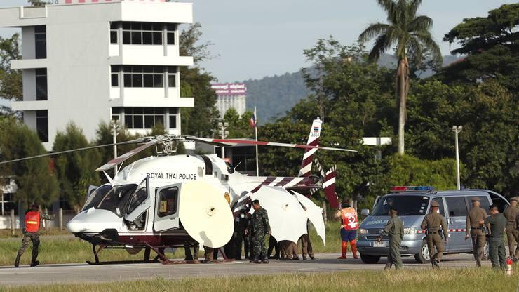 Thailandische Soldaten und Polizisten bringen einen Jungen per Helikopter ins Spital.