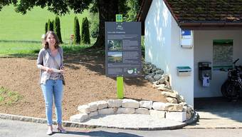 Gemeindeammann Therese Brändli spricht vor der neuen Jurapark-Tafel beim Bushäuschen in Linn. zvg