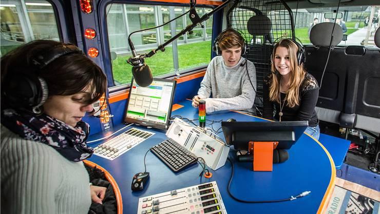Von links: Mariel Diez vom Powerup-Team instruiert Aurelio Wyss (4. Kanti) und Svenja Schraner (3. Kanti) im Radiobus.