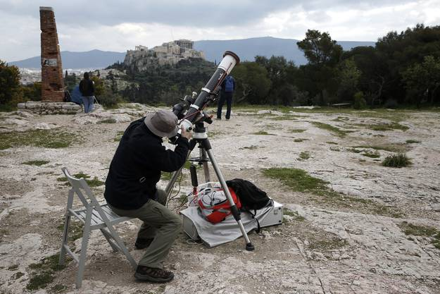 Ein Mann beobachtet mit seinem Teleskop die Sonnenfinsternis in Athen, im Hintergrund die Akropolis.
