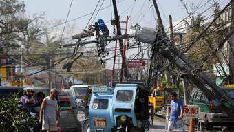 """Chaos in Iriga nach Taifun """"Nock-Ten"""":  Die starken Winde kappte Stromleitungen und kippte Masten. Nun beginnen die Aufräumarbeiten."""