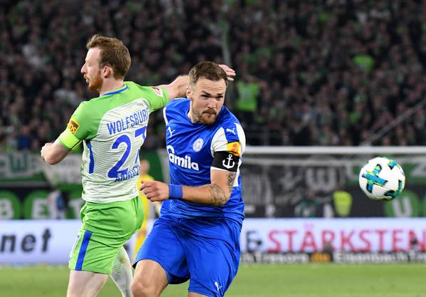 Wolfsburgs Maximilian Arnold (l) und Kiels Rafael Czichos kaempfen um den Ball.