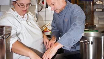 Der neue Küchenchef Peter Jörimann zeigt Seraina Gerig, wie sie die Auberginen anbraten soll. psi