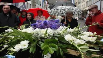 Zumindest hält die feuchte Witterung die Blumen frisch – hier der verzierte Sodbrunnen in der Rathausgasse.