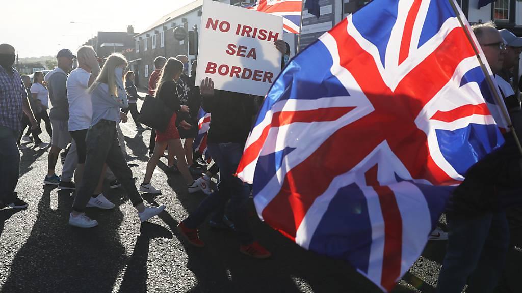 ARCHIV - Demonstranten halten britische Fahnen und ein Schild mit der Aufschrift «No Irish Sea Border» («Keine irische See-Grenze») bei einem Protest protestantischer Loyalisten gegen das sogenannte Nordirland-Protokoll. Foto: Brian Lawless/PA Wire/dpa