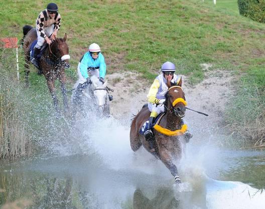 Die Pferde jagen im letzten Rennen der Saison durch den Wassergraben