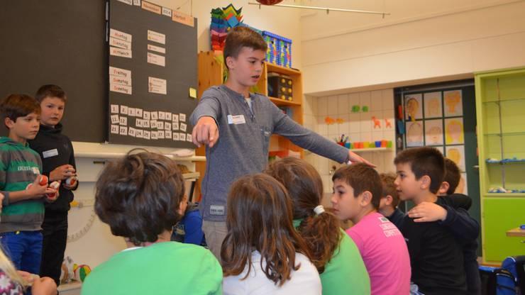 Edon erklärt, wie das Spiel geht. Die Kinder hören gut zu.