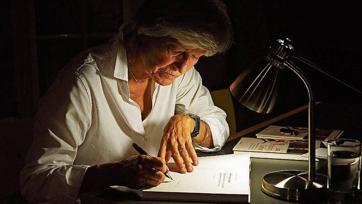 Elisabeth Binder signiert ihr Buch.