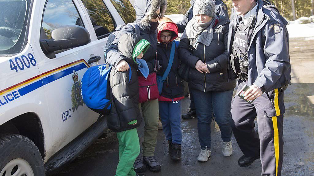 Kanadische Polizisten nehmen eine Familie von Asylsuchenden an der Grenze zu den USA in Hemmingford in Empfang.