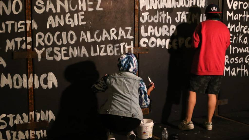 Frauen bemalen die Metallbarrieren des Nationalpalastes mit Namen von Opfern von Femiziden. Vor geplanten Protesten am Weltfrauentag haben Aktivistinnen einen langen Zaun vor dem Präsidentenpalast in Mexiko-Stadt mit Namen von ermordeten Frauen voll geschrieben.