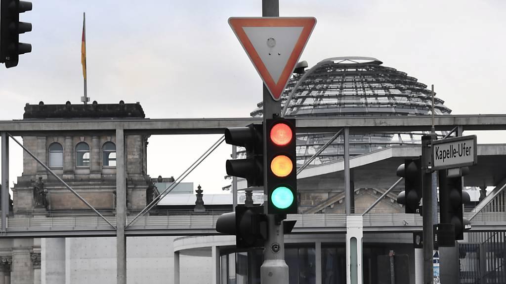 ARCHIV - Eine Ampel, an der die Farben Rot, Gelb und Grün gleichzeitig leuchten, ist vor der Kuppel des Reichstagsgebäudes zu sehen. SPD, Grüne und FDP wollen über eine mögliche Ampelkoalition verhandeln. Foto: Julian Stratenschulte/dpa